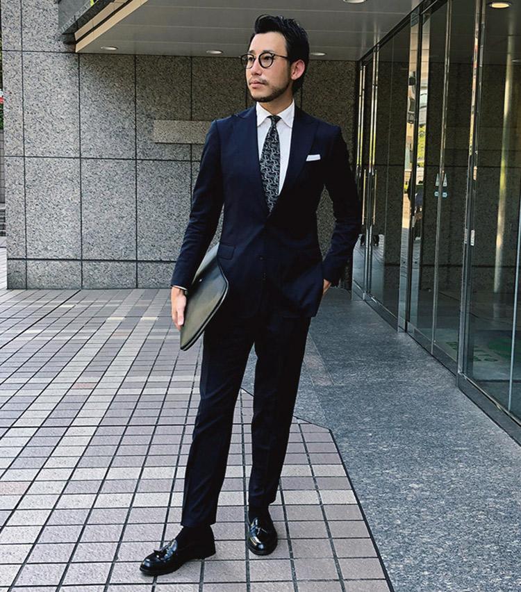 <p><b>有木 優成さん</b><br /> AT SCELTA CO.Ltd. DESIGNWORKS EC Web担当<br /> <b>エレガントな装いに細部でアクセントを注入</b><br /> 光沢感が美しいスーツに、ピークトラペルやタイでアクセントを持たせている。「シルク混のネイビー無地スーツに螺旋状のジャカードタイで色数を抑えながらエレガントなドレスタイルをイメージしました」(有木さん)<br /> <a class=