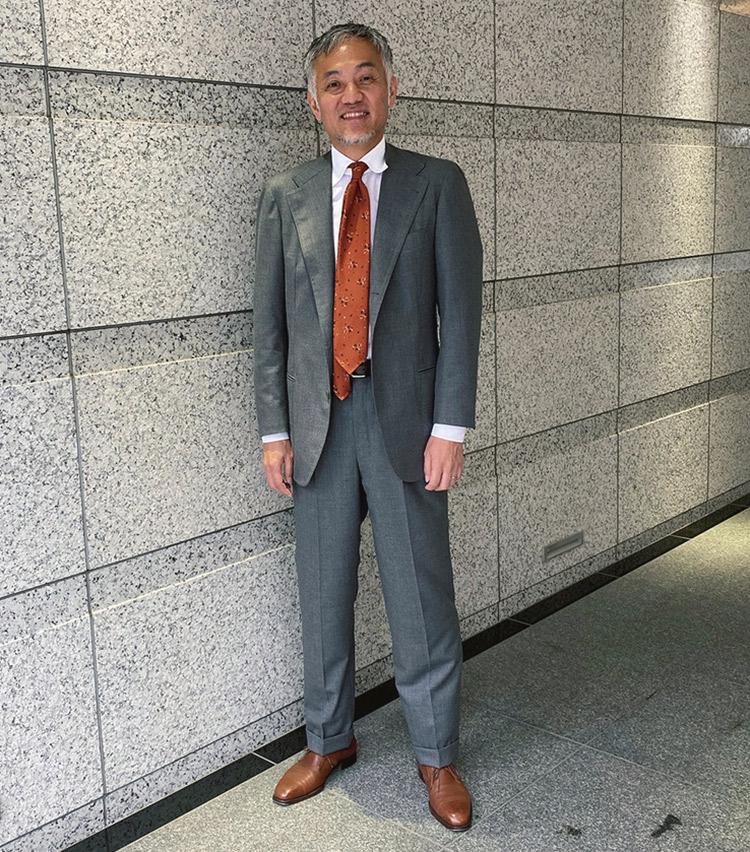 <p><b>阿部 浩さん</b><br /> レガーレ代表取締役<br /> <b>気分を上げるオレンジタイでメリハリのある一色挿し</b><br /> 取材日は雨模様。3年越しに手元に届いたという#anglofiloのスーツが映える。「タイはホーランドシェリーのスーツ生地に合わせた羽二重プリント。こんな天気の日は、気分を上げる。フレッシュなオレンジで!」(阿部さん)<br /> <a class=