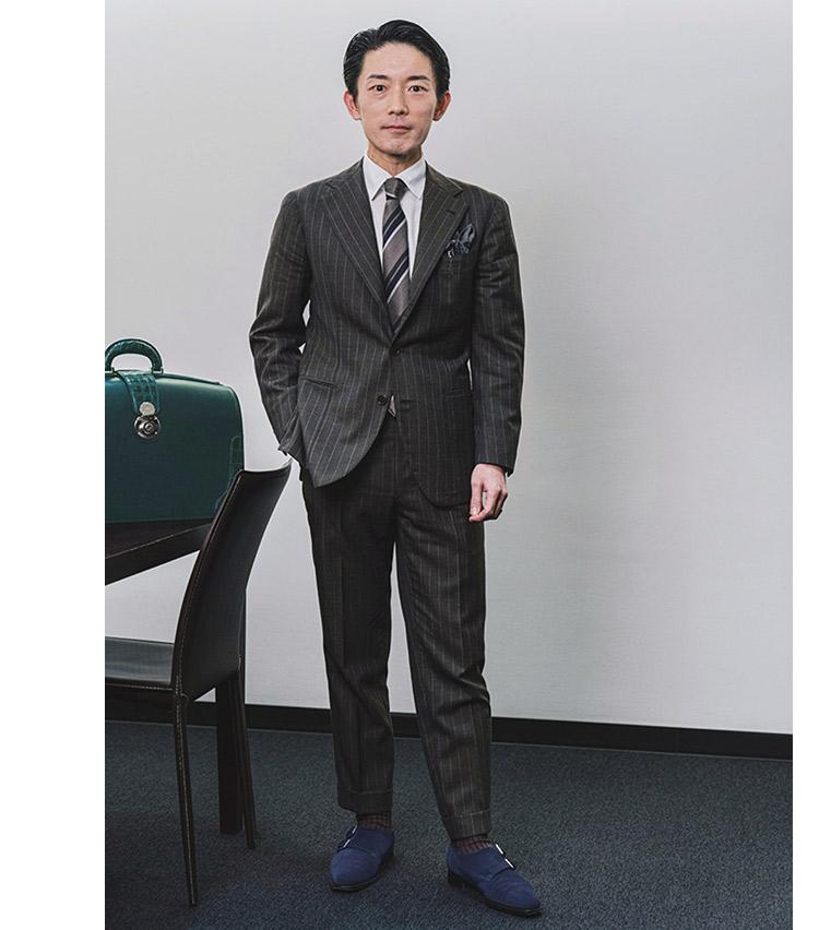 """<p><b>阿久津 隆一さん</b><br /> 大手国際会計事務所  パートナー 税理士<br /> <b>色を紡いだ、まとまりのある装い</b><br />  """"調和""""を心掛けたという阿久津さん。「スーツの柄色をネクタイのベースカラーで拾い、ネクタイのライトグレーはチーフで、紺は鞄で、カーキは足元の靴とベルトで色を拾い、調和を持たせています。」<br /> <a class="""