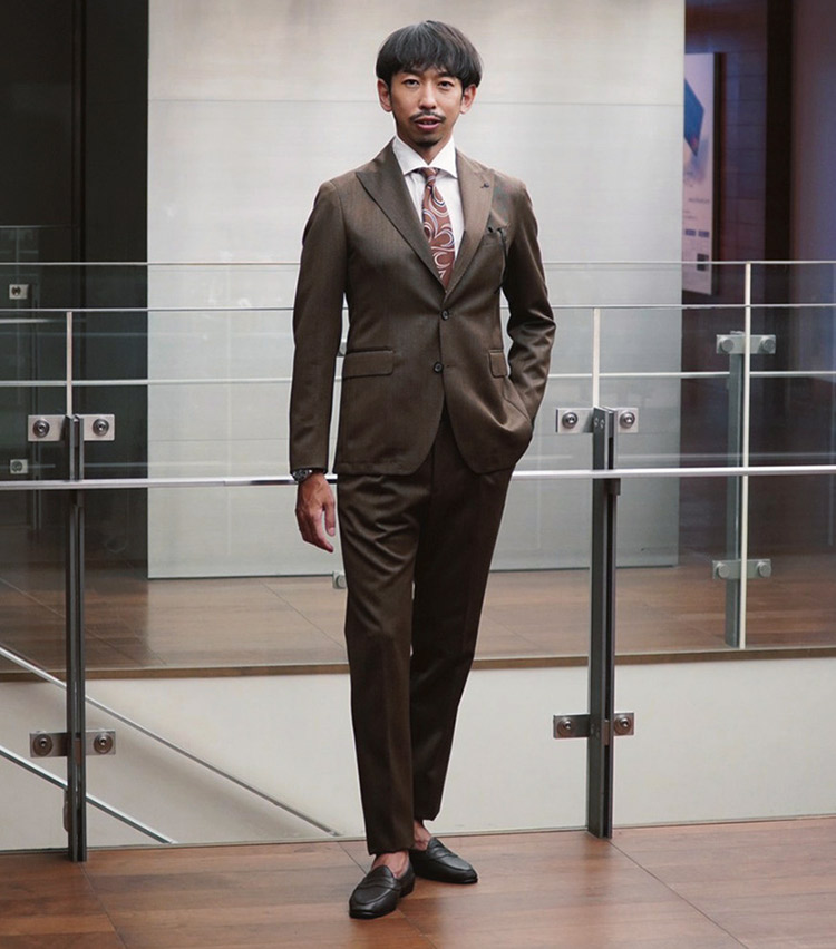 <p><b>砂賀 一行さん</b><br /> アバハウスインターナショナル マーケティング部<br /> <b>ブラウントーンで秋の先取りを</b><br /> 統一感のあるスーツスタイル。「秋をイメージしたブラウンで統一。タリアトーレのスーツはパンツのシルエットの良さに加え、ウエストに伸縮性のある素材を使用しているところがお気に入り。」(砂賀さん)<br /> <a class=