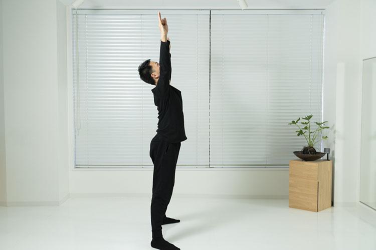 <p>肩幅よりやや広く脚を開いて立ち、棒を持った両腕を上げる。</p>