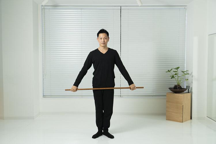 <p>肩幅よりやや広く腕を広げて棒を持って立つ。</p>