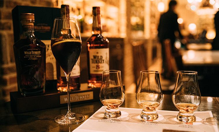 <p>テイスティング会場となったのは東京・青山にあるバー「TOKYO Whisky Library」。左はワイルドターキー8年をベースに使った同店オリジナルカクテルの「ラルゴ」。アフロディーテレッド、モナンブルーキュラソー、ハイビスカスティーをブレンドし、さっぱりとした味わいに。光を当てるとヴァイオレットカラーが際立つ。</p>