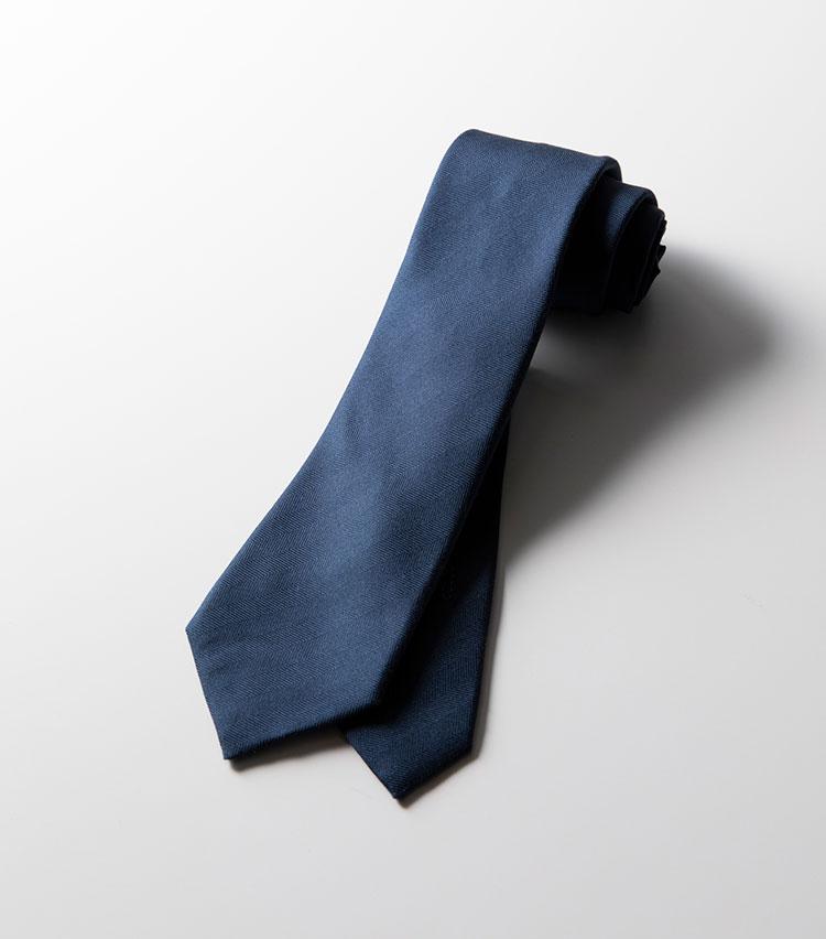 <p><strong>エルメス/ヘリンボーン織り</strong></p> <p>一見ベーシックな紺無地だが、よく見ると表情のあるヘリンボーン織り。ツイルなどよりもマットな発色が落ち着いた印象だ。さらに印象的なのは、刺繍で表現された馬のモチーフ。一筆書きのタッチがアーティスティックだ。4万6000円(エルメスジャポン)</p>