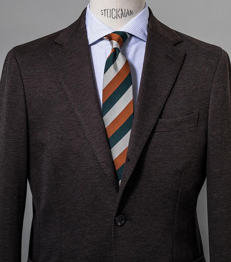 <p><strong>ブラウンスーツを若々しく見せるポイントに</strong><br /> スーツのブラウンとタイのオレンジがリンクし、グリーンが際立つ。ストライプシャツも両者の橋渡し役に。スーツ6万5000円〈オーダー価格〉/麻布テーラー(Y&Mプレスルーム) シャツ3万6000円/リングヂャケット ナポリ(リングヂャケットマイスター206 青山店) ※タイは上の画像[右]と同じ。</p>