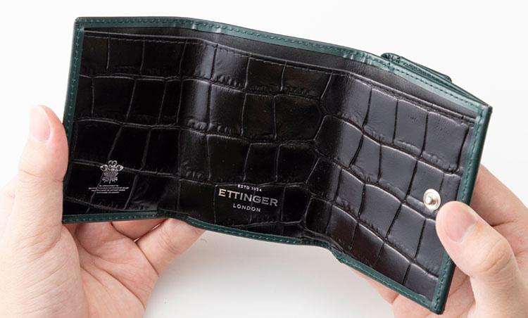 <p>《エッティンガー/開いたところ》<br /> グリーンの外装とのコントラストが色気を主張。内装にクロコの型押しレザーを配したこちらのモデルは阪急限定。</p>