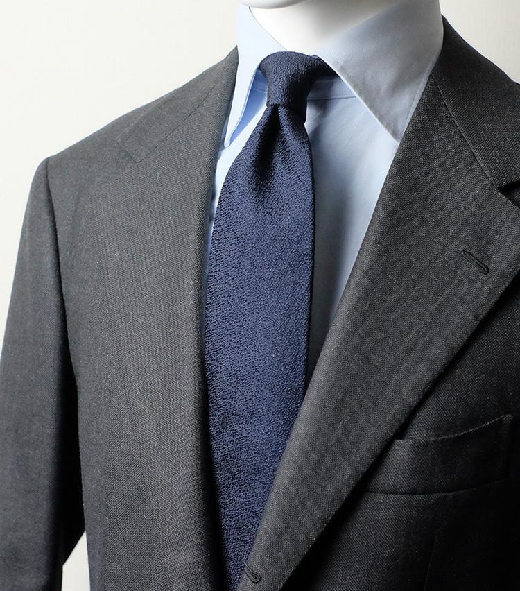 <p><strong>砂子調<br />ヴィンテージ調の味わいある表情</strong><br /> 和装用品でしばしば用いられる「砂子」のような組織に仕上げたシルクタイ。ヴィンテージテイストの隆盛に伴って増えてきた素材だ。ランダムな織り感があるため、無地ながら表情豊かなのが何よりの魅力。こちらの写真のように、すべて無地もので統一した装いでもアクセントが効く。</p>