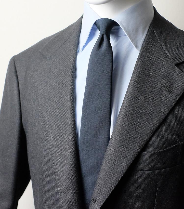 <p><strong>バラシャ<br />独特のマットな質感がミニマルな装いを築く</strong><br /> 少々変わり種の素材。フォーマルスーツなどに用いられるバラシャで仕立てた一本は、プレーンな質感ながら独特のマットさが特徴。細めに設定された大剣幅ともあいまって、非常にミニマルな印象を醸し出してくれる。もともと控えめな紺無地タイの中でも、特にストイックな印象だ。</p>