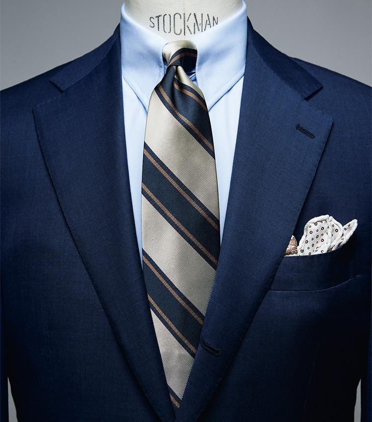 """<figure><figcaption>シャツ2万2000円/ギ ローバー、タイ1万7000円/フランチェスコ・マリーノ、チーフ6800円/パオロ アルビザッティ(以上ビームス ハウス 丸の内) スーツは上画像[NAVY SUIT style]と同じ</figcaption></figure> <p></p> <p><strong>NAVY SUIT style<br />「イエローストライプのタイで'80〜'90年代的アメリカンを意識」――中村さん</strong><br /> 「1980〜'90年代のアメリカ的なテイストを盛り込んだスタイリング。キーアイテムはイエローのストライプが効いたタイ。独特の華やかさが特徴で、1980〜'90年代的なムードを醸し出します。ちなみに当時、イエローの入ったタイは""""モテる服装""""に欠かせませんでした(笑)。シャツは青無地に。柄タイを合わせる際は、白より青のほうが柔らかな印象になります」</p>"""