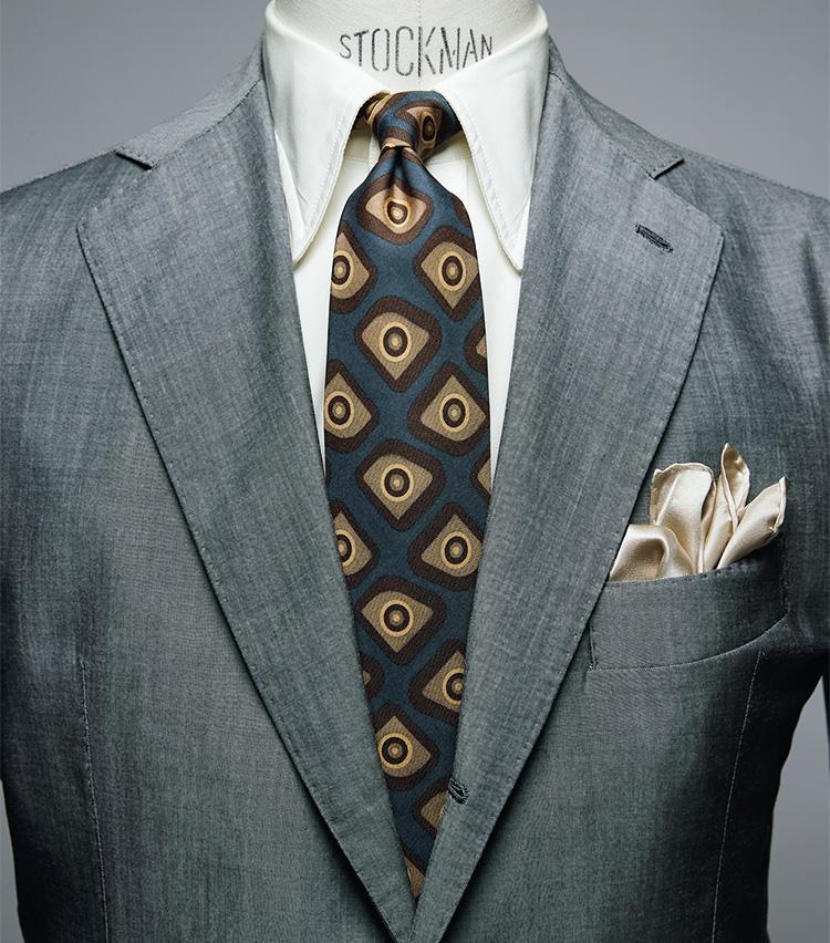 <figure><figcaption>シャツ2万5000円/ドレイクス、タイ1万7000円/フランチェスコ・マリーノ、チーフ3800円/ビームスF(以上ビームス ハウス 丸の内) スーツは上画像[GRAY SUIT style]と同じ</figcaption></figure> <p></p> <p><strong>GRAY SUIT style<br />「クリーム色のシャツでグレースーツを柔和に」――中村さん</strong><br /> 「シャツは一見、白無地のようですが、実は薄いクリーム色。白よりも柔らかい印象を醸し出したいときに便利なアイテムです。そんな雰囲気に合わせて、ネクタイも軽やかなプリントタイを選びました。色柄を多用しているためレベルが高く感じるかもしれませんが、タイのベースカラーをスーツと、柄色をシャツやチーフの色とリンクさせて調和を図っています」</p>