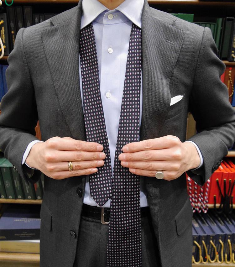 <p><strong>1. START!</strong><br /> 大剣が左にくるようにシャツにネクタイを通す。小剣はベルトより上にくるぐらい。</p>