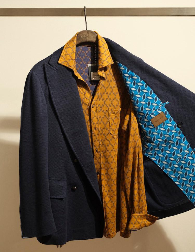 <p>ネイビージャケットには、これくらいパンチのあるニットシャツを合わせても◎。イエローの色が微妙にくすんでいるのでシックにまとまる。ダブルの前はあえて開けてカーディガン感覚で羽織り、中のニットシャツを見せるイメージ。</p>