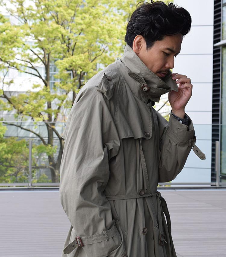<p><strong>チンフラップを留めた姿も美しい</strong><br /> ボタンを上まで留めてウエストベルトを締め、襟を立ててチンフラップを留めた男らしい着こなしもサマになる。たっぷりとした袖にメリハリのあるXライン、なだらかな肩周りがあいまって、クラシックな美しさが際立つ佇まいに。</p>