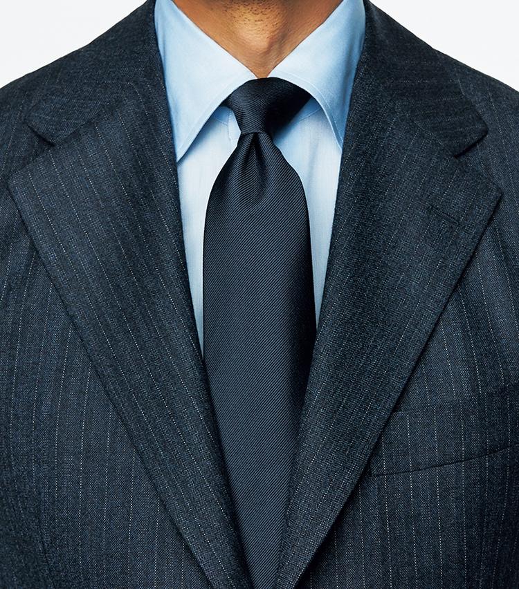 <p><strong>表情豊かなストライプスーツをシックに受け止める</strong><br /> シャツもブルーで端正なワントーン</p>