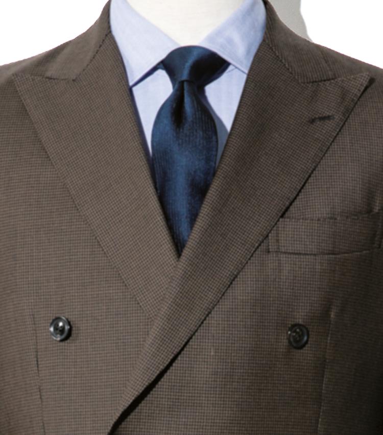 <p><strong>茶スーツを知的に見せるネイビーの胸元</strong><br /> 梳毛スーツ×シルクタイでエレガント</p>