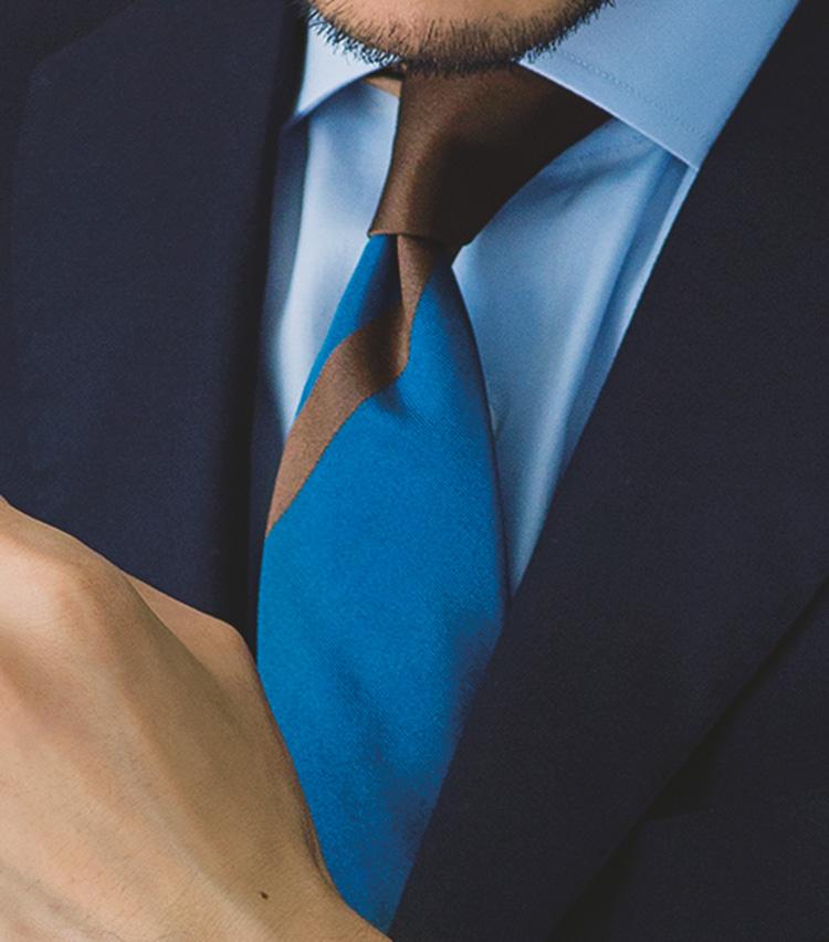 <p><strong>[STYLE5]茶系の差し色を効かせたブルーグラデ</strong><br /> 「ライトブルー、青、紺色のブルーグラデーション。スーツを濃い色にして、ネクタイを中間の色にするとバランス良好。茶の差し色が、知的すぎて近寄りがたい雰囲気を解消します」</p>
