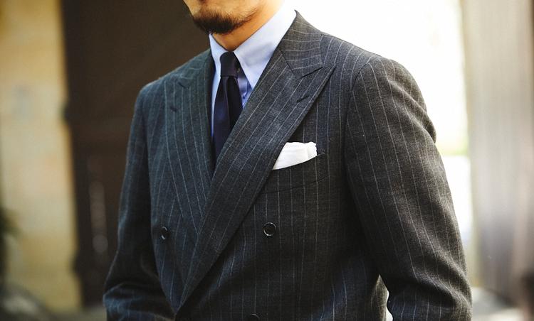 <p>グレースーツにブルーシャツ、ネイビーソリッドタイに白リネンチーフという王道かつクラシックな胸元。</p>