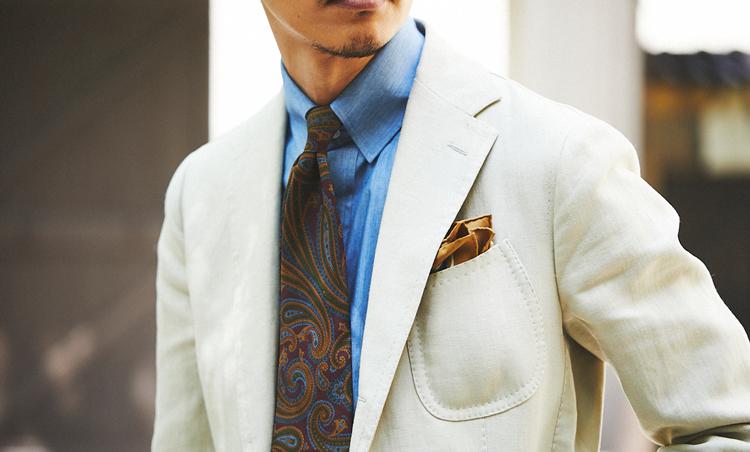 <p>仕立ての軽いアイリッシュリネンスーツに、タブカラーのシャツ、大柄ペイズリーのプリントタイで1950~60年代のアメリカンラグジュアリーを意識。</p>