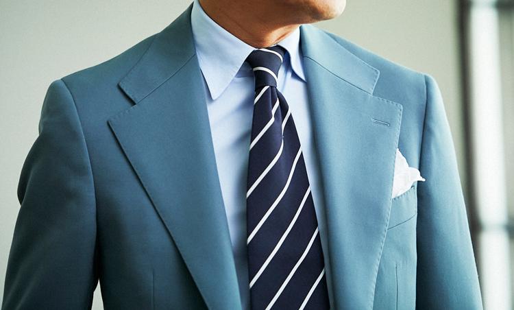 <p>遠目にはグレーのようで、実はグリーンがかった絶妙なカラーのスーツ。ワイドめのラペルには、ネイビー×紺の細ストライプタイでバランスを。</p>