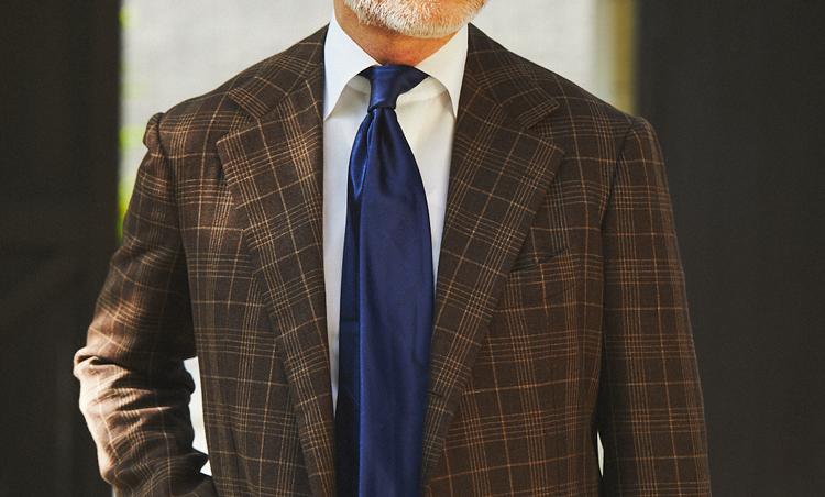 <p>盛夏のアズーロ エ マローネの王道的胸元。濃いめのこげ茶のチェックジャケットに、ストイックなネイビーソリッドタイでシックな印象に。無造作な雰囲気のノットも達人感あり!</p>