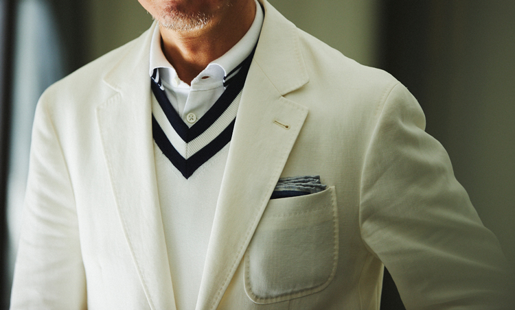 <p>真っ白でなくオフ白(パナマ)カラーのジャケットに、同系トーンのチルデンニットが好相性。ポロの襟にもネイビーのラインが入っていて、ニットのVゾーンとのバランスも◎。</p>