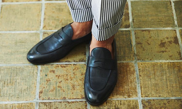 <p>ネイビーコードレーンのパンツの足元は、柔らかレザーのローファーで軽やかさを演出。</p>