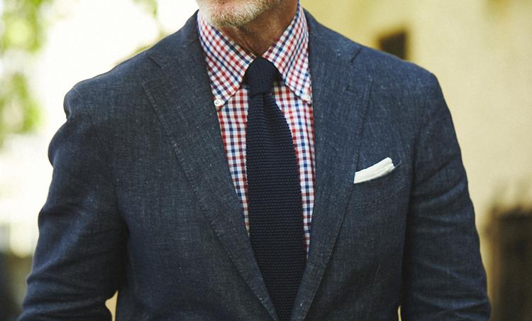 <p>リネンスーツのデニムカラーにリンクさせて、ブルーと赤のギンガムチェックシャツにネイビーニットタイでカジュアル感のある涼感Vゾーンが完成。</p>