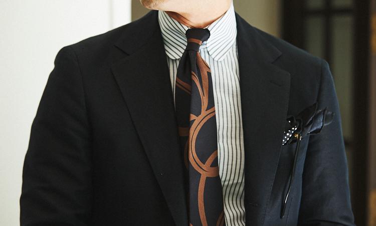 <p>重たく見えがちな黒スーツは、リネン100%のシャツを合わせることで涼感UP。シャツのストライプのピッチが細めなので、タイは大柄のシルクプリントをチョイス。黒と相性のよいブラウンが、胸元にエレガントな存在感を演出。</p>