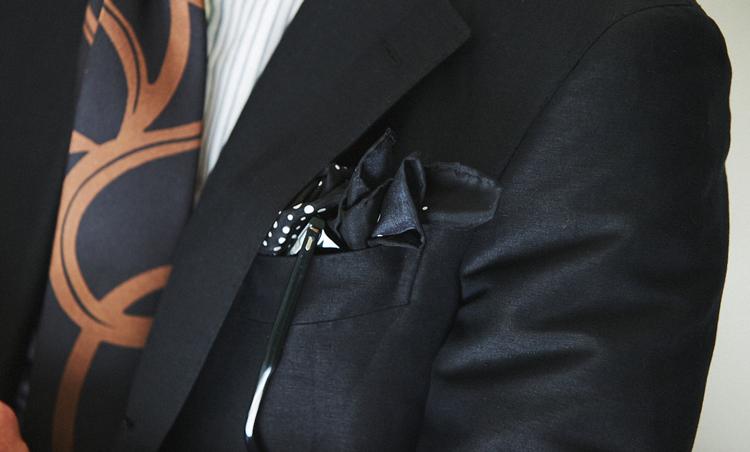 <p>黒のシルクプリントチーフとサングラスをさりげなく挿しているのも、胸ポケの絶妙なアクセントに。</p>