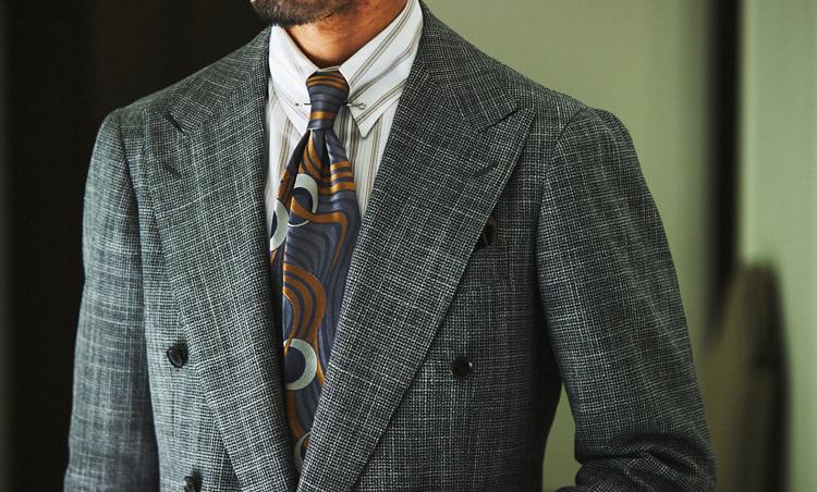 <p>ダブルスーツのグレンチェック柄が細かいので、シャツのブラウンストライプはやや間隔広めに。ここに大きめの幾何学柄タイを合わせることで、インパクトを出している。</p>