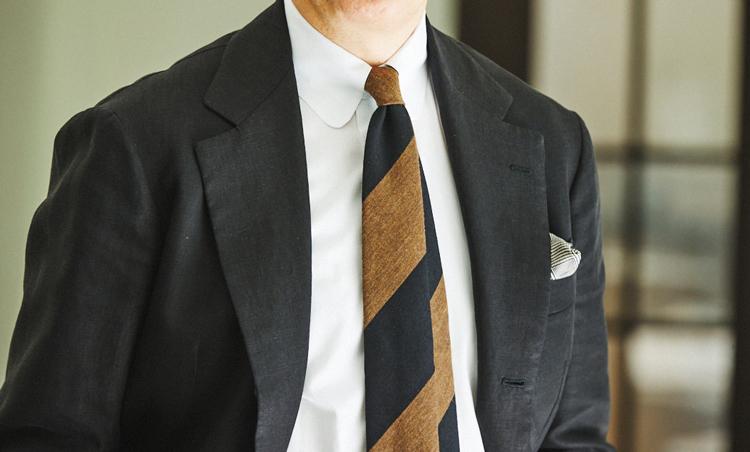 <p>白シャツの襟元はラウンドタブカラーで、タイのノットもコンパクトに。黒と茶のワイドレジメンタルタイが、黒リネンスーツに映える。</p>