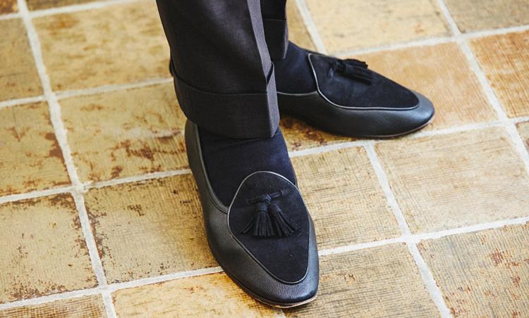 <p>足元はブラックレザーとスエードのコンビスリッポンで軽さを出した。スーツスタイルなので、ソックスをきちんと履くことで上品をキープ。</p>