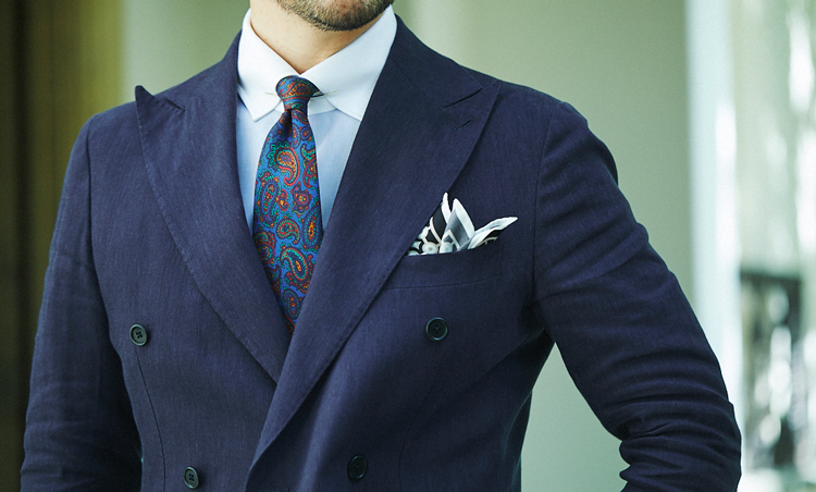 <p>涼感あるリネンのネイビースーツには、クレリックのシャツに明るめブルー基調のペイズリータイで華やかさをプラス。ゴールドのカラーピンを使ってノットはコンパクトに。</p>