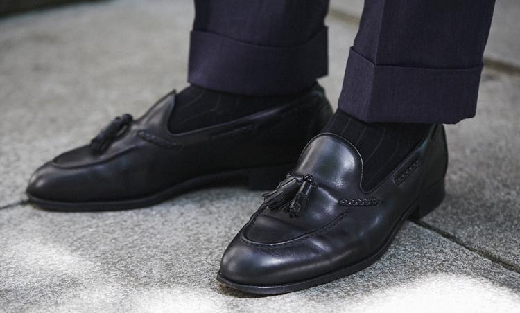 <p>ストイックなスーツスタイルの足元は、エドワード グリーンの黒タッセルローファーで硬派に。</p>