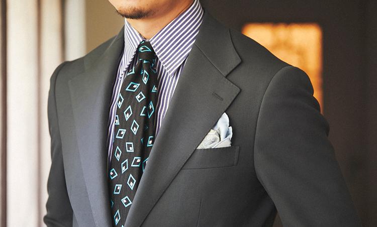 <p>ブルーグレー調のスーツに合わせて、ブルーのストライプシャツに幾何学柄のタイでメリハリを出している。</p>