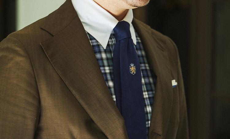 <p>オリーブグリーンのスーツの色を拾った、チェックのクレリックシャツでスポーティに。タイはネイビーのワンポイントにすることでシックさも加えた。</p>