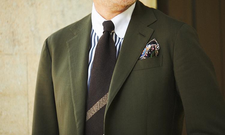 <p>強撚のオリーブカラーのスーツの胸元は、クレリックシャツとウールタイでクラシックに合わせた。シャツとタイのストライプのピッチ幅をずらしているのもポイントだ。</p>