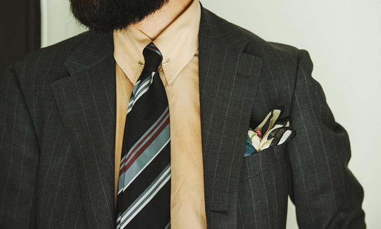 <p>グレーベースのスーツに、白やブルーでなく、ベージュトーンのシャツを合わせたのが粋。襟元もピンホールカラーで、タイのノットをかなりコンパクトに。タイと同系トーンの柄チーフで華やかさを出しているのもポイント。</p>