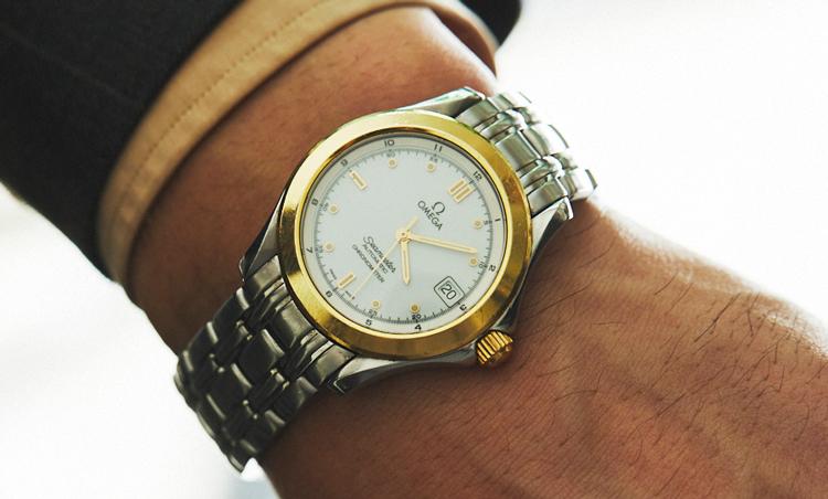 <p>時計は、義父から譲り受けたというオメガのシーマスター。「SSケースにゴールドのベゼルが際立つドレッシーなコンビモデルですが、このシルバー×ゴールドというカラーリングに便利さを感じています。アクセサリーがシルバーでもゴールドでも、この時計との重ね着けならバランスを崩すことなく、カラーピンやブレイシーズ、リングなど、合わせられるアクセサリーの幅も広がります。ヨーロッパでは装飾品は代々受け継がれるものですが、次々と新しいものを買うのではなく、サスティナブルな観点からも僕も愛情をもって受け継ぎながら次の世代に残していきたいと思います」</p>