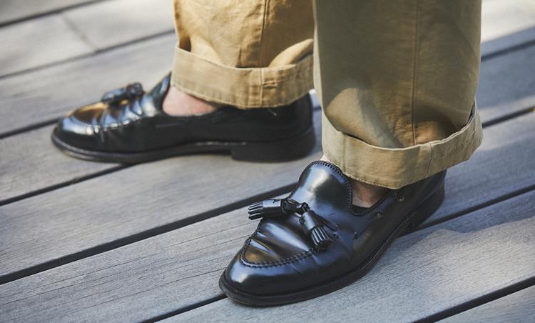 <p>足元は、オールデンの黒タッセルローファーを素足履き。ニットポロとの相性も抜群。</p>