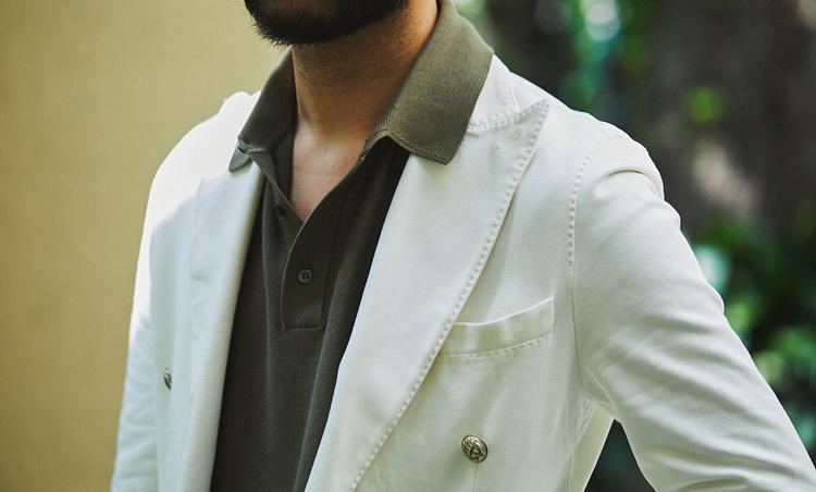 <p>オフ白ジャケットにカーキのニットポロを合わせて渋みをプラス。襟はラペルの上にアウトしてカジュアルな印象に。</p>