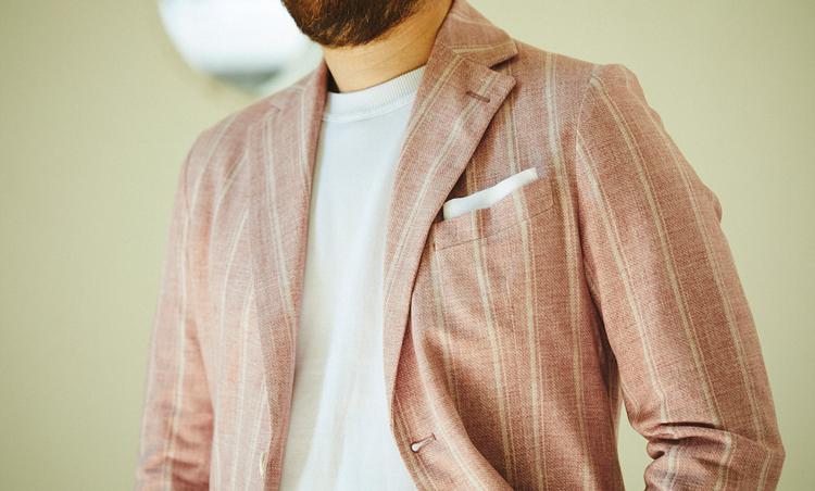 <p>一見派手なピンク地ベースのジャケットは、ストライプの白を拾ってインナーのTシャツも白で合わせた。白チーフを挿すことでカジュアルな合わせにも少しドレスマインドをプラス。</p>