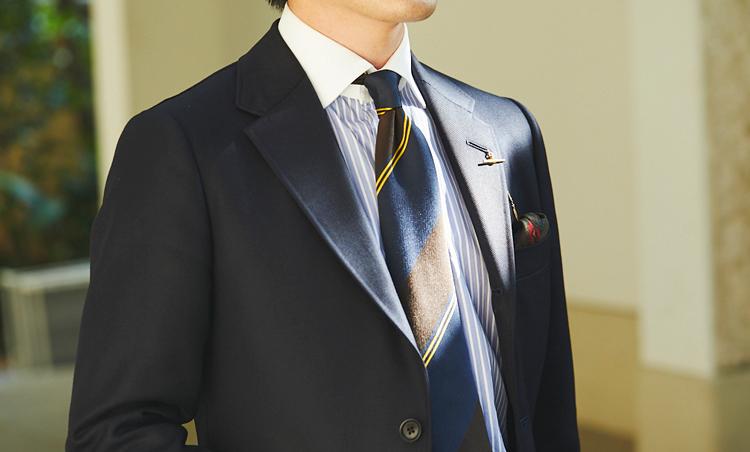 <p>アメリカの1960年代のトラッドなサックスーツでの着こなし。「自分のスタイルを貫くことで、晴れの場でも自身のある振る舞いができるのではないかと思います。シャツは涼し気にみえるようにブルーのストライプシャツで、ネクタイは芯地の薄いものを合わせました」正統派のアズーロ エ マローネ的Vゾーンだ。</p>