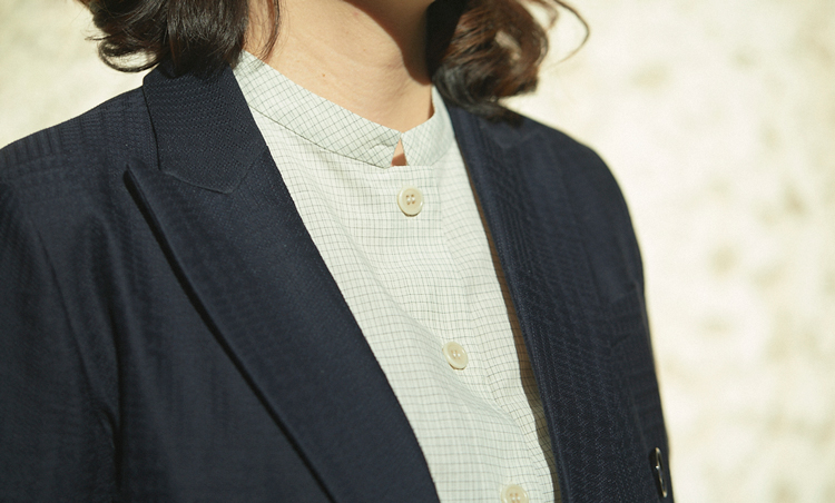 <p>アスペジのバンドカラーのシャツは、実は細かなグラフチェック柄。「ジャケットの織り柄ウインドウペーンは柄が大きめなので、ピッチをずらして柄が喧嘩しないようにしました」</p>
