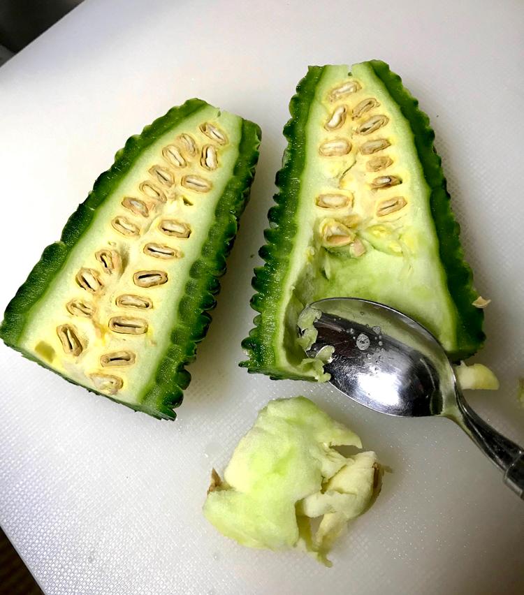 <p>2. 半分に切ったゴーヤはわたと種をスプーンで取り除く。</p>