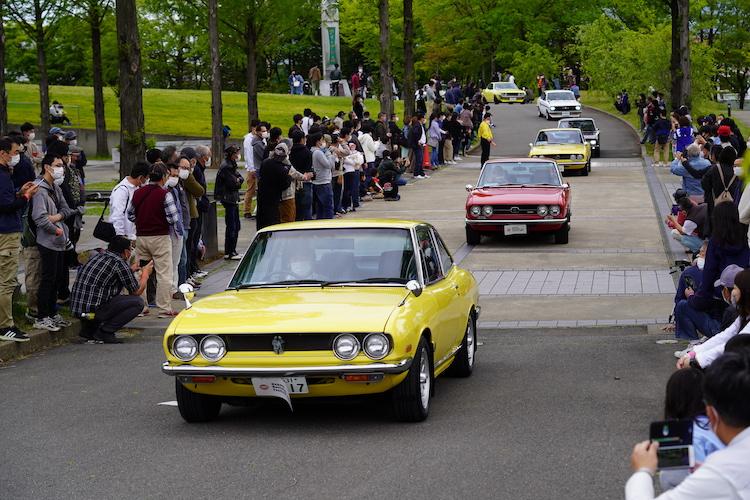 <p>エムウェーブ外周路をパレードする、恒例の「ノスタルジックカーパレード走行会」。</p>