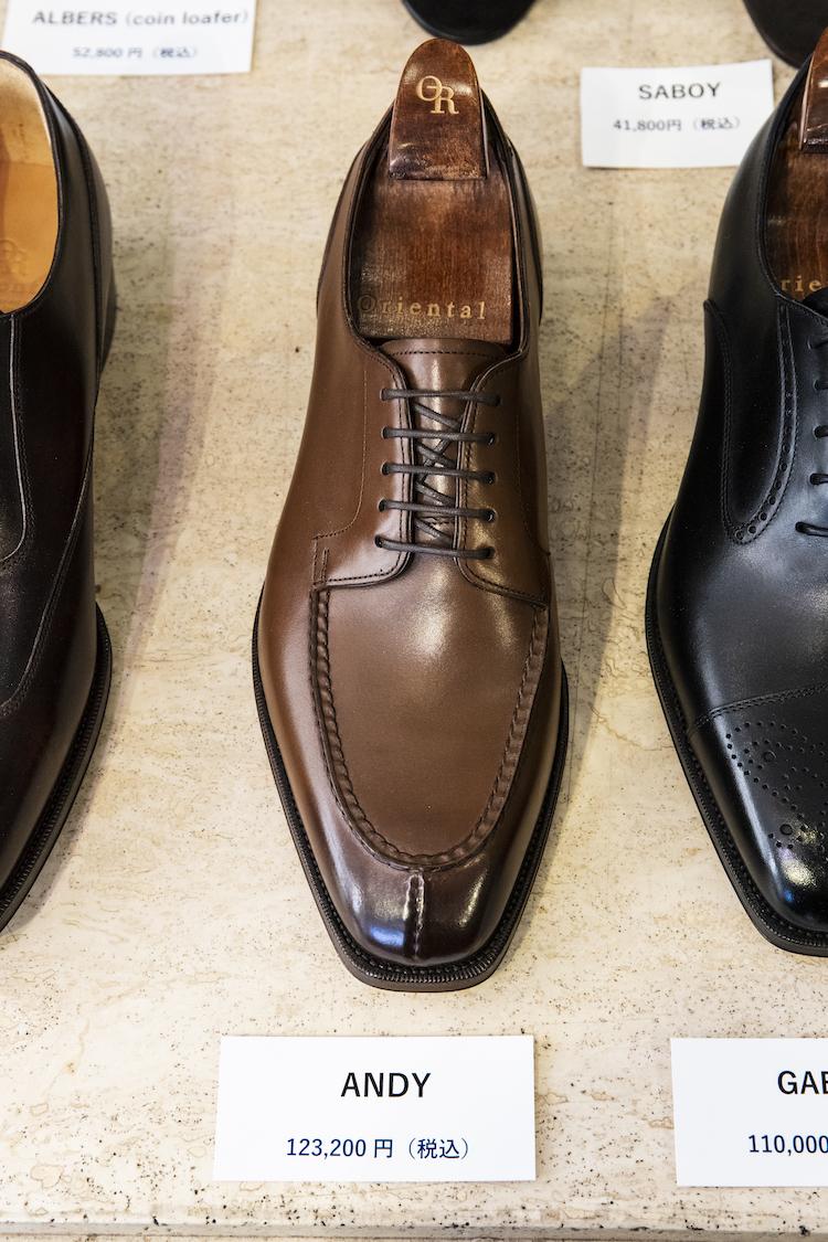 <p><strong>ANDY</strong><br /> ハンドソーンウェルテッド製法でお作りしたトップグレードラインのモデル。本来革靴のなかではカジュアルシューズに位置づけられるUチップ型だが、スキンステッチが施され、また、ソールウエストは立体感あるフィドルウエスト仕様に、さらにウエストのコバは、出し縫いが隠されており、抜群にエレガントな雰囲気に仕上げられている。ラストはボールジョイント部が薄く、甲も低め、踏まずから踵にかけても絞り込んだ、メリハリのあるクラシック系のラスト「1204」を使用。アッパーは上質なヨーロピアンバーニッシュカーフを、ライニングはディアスキンを使用。専用シューツリー付き。12万3200円</p> <p><a class=