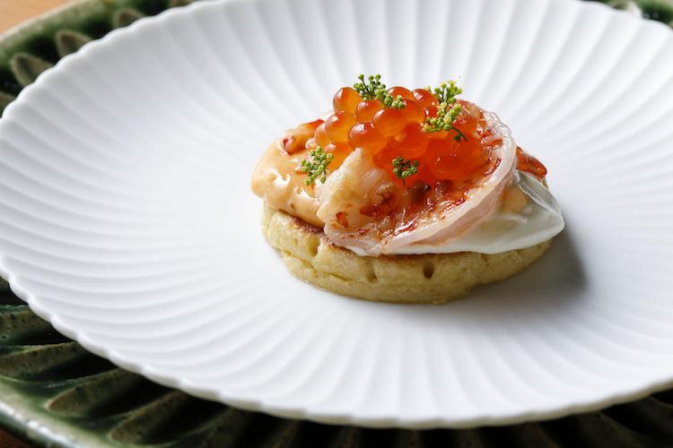 <p>ランチコースより。コースのスターターでシグネチャー料理のひとつ「八坂パンケーキ イクラと海老」。モチッとして甘みを感じる生地と海の幸の取り合わせが絶妙。</p>