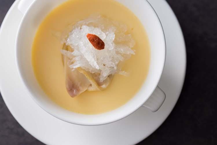 <p>滋味深い烏骨鶏卵を使った滑らかな口当たりの茶碗蒸し。ツバメの巣と出汁にも使われている蛤が添えてある。</p>