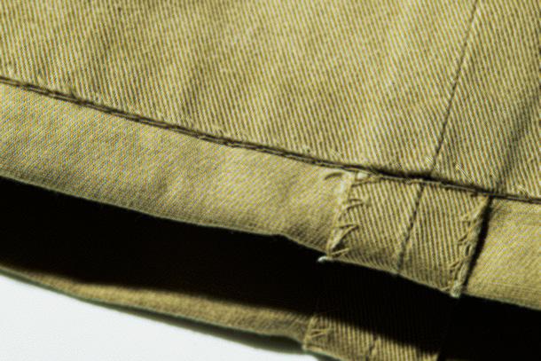 <p><strong>裾の処理も独特</strong><br /> 「現在のチノパンはタタキで裾を仕上げるのが一般的ですが、こちらはシングル仕上げになっています。まつり縫いのステッチが表側からはっきりと見えるのも特徴的で、ベルトループ同様に素朴ながら味があります」</p>